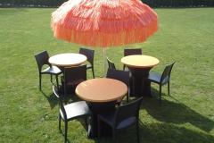 Oranje terras verhuur met zwarte stoel en oranje raffia parasol